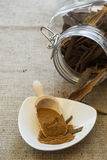Cassia powder. In bowl and jar with sticks on background royalty free stock photography