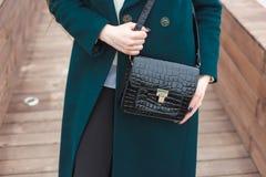 Cassic coat with leather handbag Stylish fashion model outdoor. Stock Photo