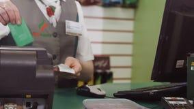 Cassiere Checks Bonus della donna sulla carta nel negozio della stazione archivi video