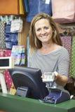Cassiere femminile At Sales Desk con il terminale POS di credito Immagini Stock