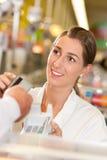 Cassiere in supermercato che cattura la carta di credito Fotografia Stock