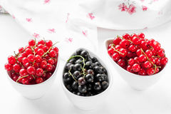Cassis rouges et dans un plat blanc sur un fond clair Images stock