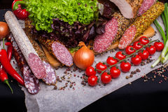 Cassoulet. Cold cuts from different kinds of meat and vegetables on a dark background stock photo