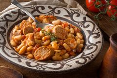 Cassoulet with Sausage, Bacon, Beans and Tomato. A delicious hearty cassoulet with artisanal sausage, tomato, bacon and white beans on a rustic tabletop Stock Images