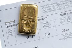 Cast gold bar weighing 250 grams on a background of a certificate stock image