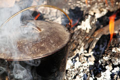 Cast Iron Bean Pot. Cooking lunch on an open campfire Stock Photo