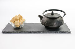 Cast-iron black teapot and several cane sugar cubes in glass bow Royalty Free Stock Photo
