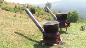 Cast iron bowls for boiling water. Two cast iron bowls with improvised wood burning stove under them for boiling water in a hilly outdoor scenery stock footage