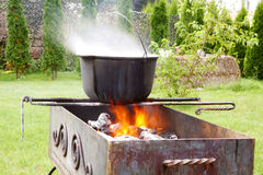 Cast iron cauldron over an open fire. Royalty Free Stock Photography