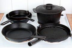 Cast iron cookware. Seasoned cast iron cooking utensils on electric stove Stock Photos