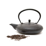 Cast iron eastern black teapot and scattered dry t Royalty Free Stock Photos