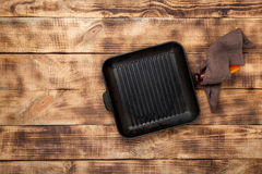 Cast iron frying pan grilling on a wooden table stock images
