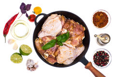 Cast-iron frying pan with marinated chicken thighs for frying Royalty Free Stock Images