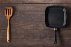 Cast iron frying pan and spatula on the wooden background. Royalty Free Stock Images