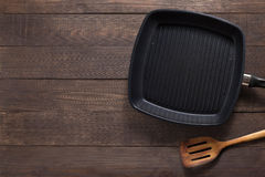 Cast iron frying pan and spatula on the wooden background. Copy Stock Images