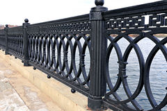 Cast iron grate fence on the embankment Stock Images