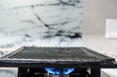 Griddle on a gas stove. Cast iron griddle sitting on a gas fired stove top Stock Images