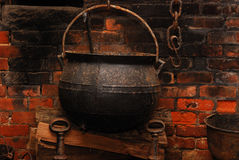 Cast Iron Kettle. This is a rustic image of a cast iron kettle, with a brick wall back round. The image was taken in a fireplace and contains some elements Royalty Free Stock Photo