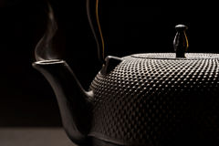 Cast-iron kettle with smoke. Black cast-iron tea in Chinese style, from the spout of which there is smoke Stock Photo
