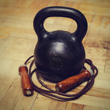 Cast iron kettlebell and leather jump rope. Black cast iron kettlebell and leather jumping rope at old parquet floor of room. Healthy lifestyle and physical Royalty Free Stock Photos