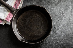 Cast iron pan on black. Cast iron pan on rustic black stone background close up - empty black frying pan frying skillet with copy space Stock Photo