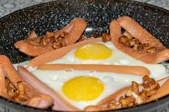 Cast-iron frying pan with fried eggs, sausage, mushroom and beans on wooden table. Top view royalty free stock images