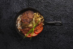 Cast-iron pan with meat, high angle view. Black background Royalty Free Stock Photos