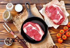 Cast iron pan with raw ribeye steak on wooden background. Royalty Free Stock Images