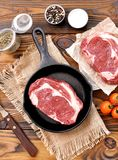 Cast iron pan with raw ribeye steak on wooden background. Royalty Free Stock Photos