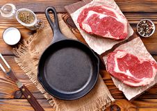 Cast iron pan with raw ribeye steak on wooden background. Stock Photos