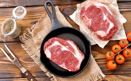 Cast iron pan with raw ribeye steak on wooden background. Stock Image