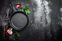 Cast iron pan and spices on black metal culinary background. View from above royalty free stock image