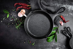 Cast iron pan and spices on black metal culinary background Royalty Free Stock Images