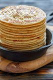 Cast iron pan with stack of fresh pancakes Royalty Free Stock Images