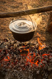 Cast iron pot on the fire burning logs Stock Photo