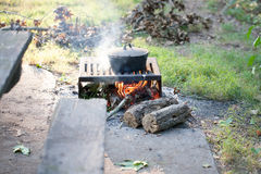 Cast iron pot on open flame camping. Cooking outdoors royalty free stock photo