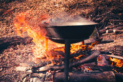 Cast iron pot outdoors, cooking on a fire. Stock Photos