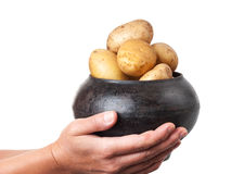 Cast iron pot with a potato in the hands Royalty Free Stock Photography