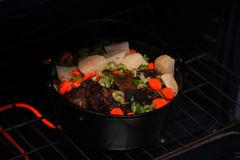 Cast Iron Pot Roast. With vegetables cooking in an electric oven stock photography