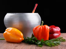 Cast iron pot with wooden spoon and varicolored peppers Royalty Free Stock Photo