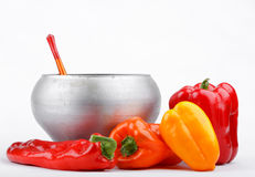 Cast iron pot with wooden spoon and varicolored peppers Stock Photography