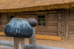 Cast iron pots on a fence near a   farmhouse Stock Image