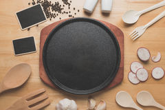 Cast Iron Sizzling Steak Plate,Rural kitchen utensils on wooden table Royalty Free Stock Photo