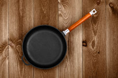 Cast Iron Skillet. Empty cast iron skillet on a wooden table closeup, top view Royalty Free Stock Images