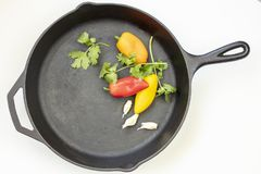 Cast Iron Skillet with red, yellow and orange peppers, parsley and garlic royalty free stock image
