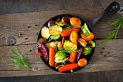 Cast iron skillet of roasted autumn vegetables. Against a rustic dark background royalty free stock images