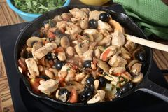 Skillet of Tuscan Chicken. A cast iron skillet with Tuscan Chicken dinner Royalty Free Stock Photography