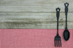 Cast iron spoon and fork on red gingham tablecloth with wood background Royalty Free Stock Images