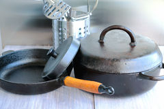 Cast iron and stainless steel cookware on a wooden table. Stock Photos