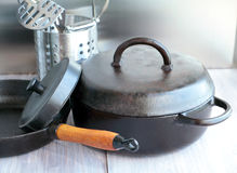 Cast iron and stainless steel cookware on a wooden table. Royalty Free Stock Images